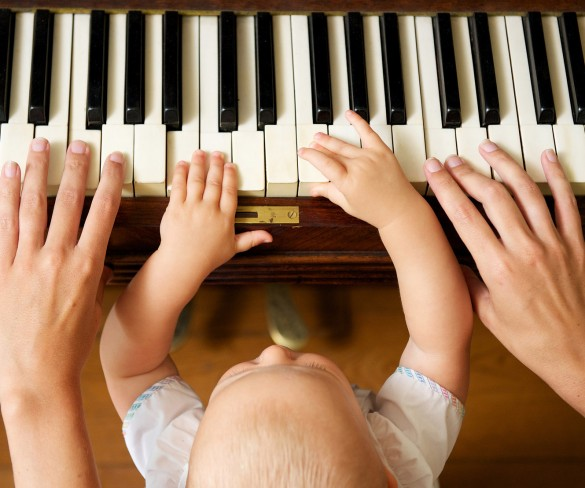 Closeup portrait of a baby learning to play piano with mother - from above